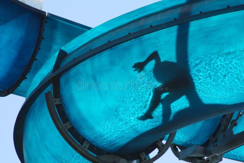 下滑水滑道的蓝色孩子 免版税库存照片