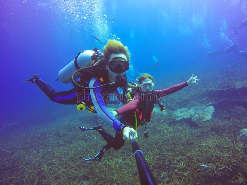 水下的佩戴水肺的潜水selfie射击用selfie棍子 蓝色深海 图库摄影