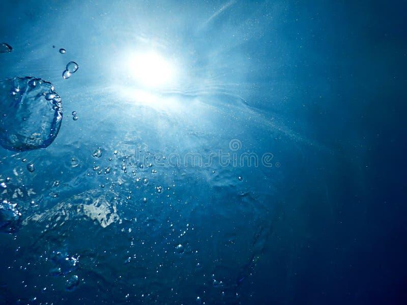 水下的泡影阳光通过水表面 水下的ba 库存照片
