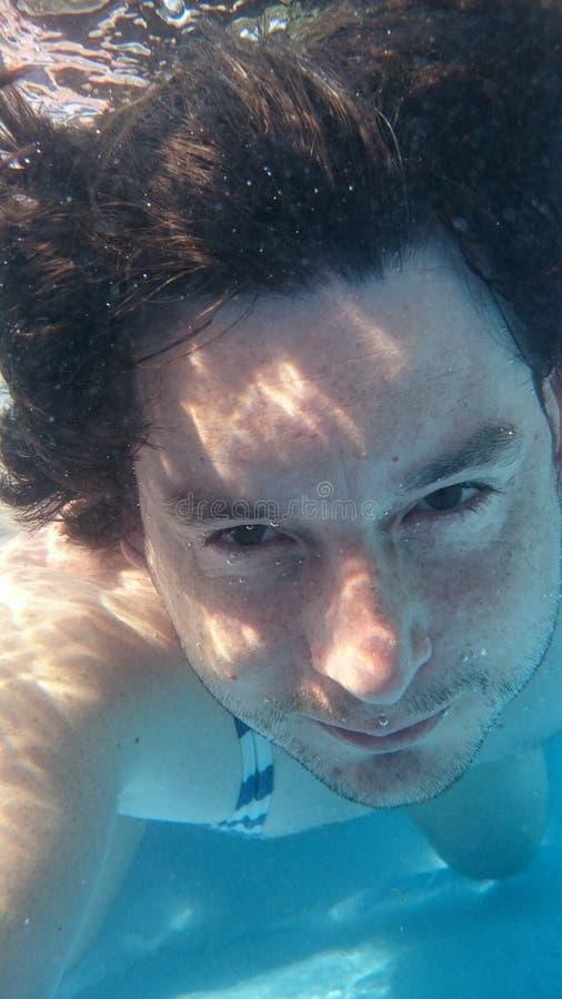 水下的游泳池的人 从特写镜头画象正面图的男性潜水 库存照片