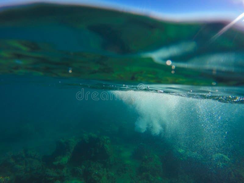 水下的风景用上面自然水分裂、蓝天和下面绿色水 免版税库存图片