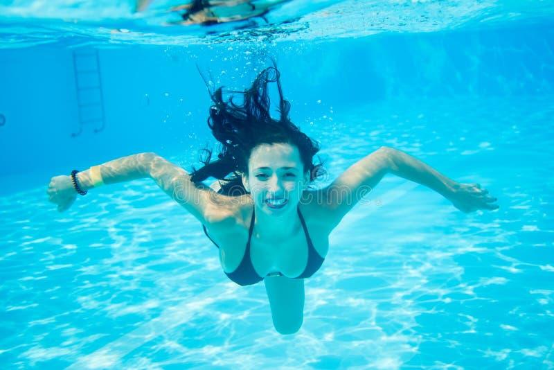 水下的画象微笑的女性佩带在游泳池,美丽的绿松石水的黑游泳衣 图库摄影