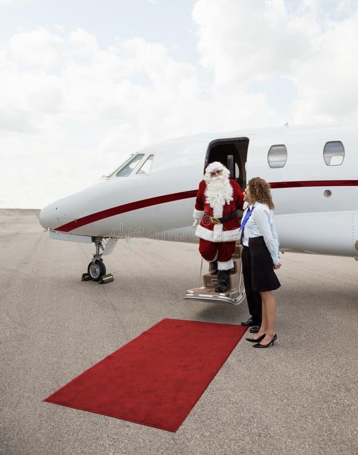 下船私人喷气式飞机的圣诞老人,当飞行员和时 库存照片