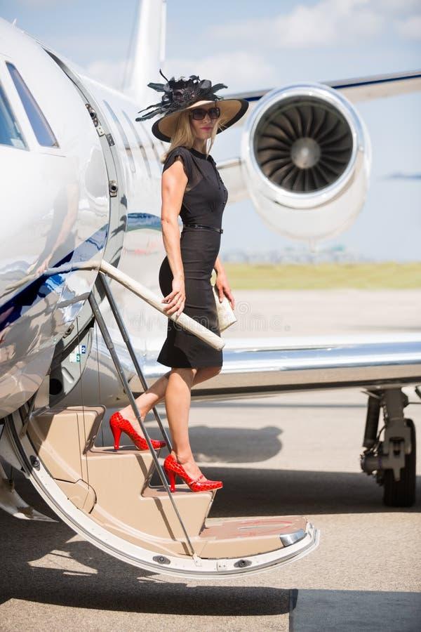 下船私人喷气式飞机的富裕的妇女在机场 免版税库存照片