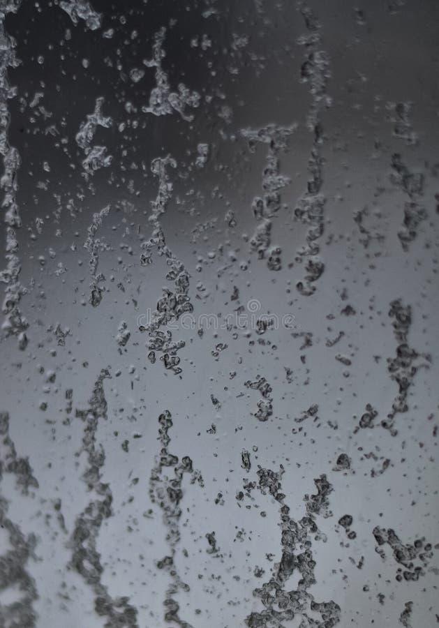 下落的特写镜头在流动下来在软的背景的玻璃在雨以后和雪的 免版税图库摄影