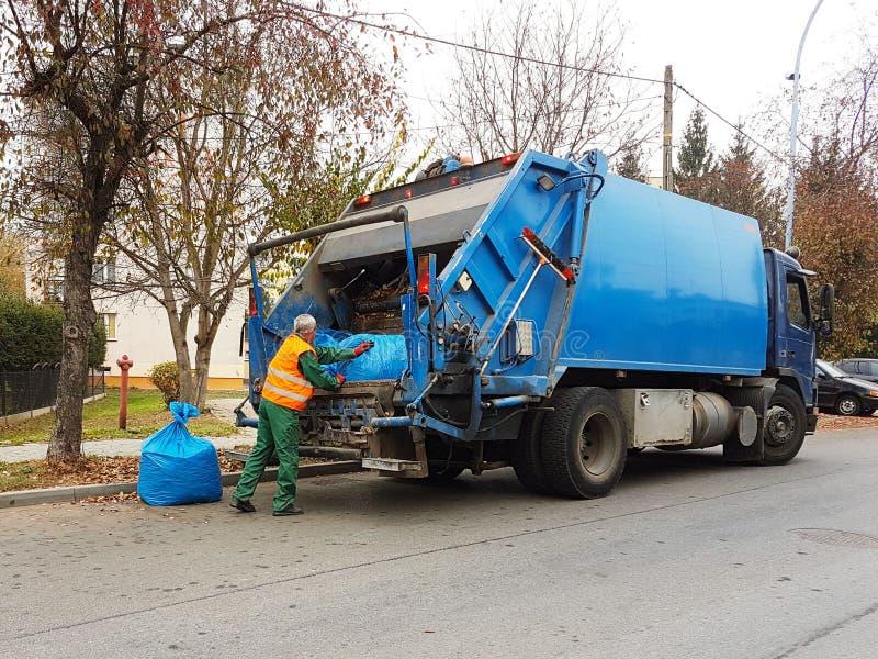 下落的秋叶处置在城市 国内垃圾的汇集和运输由市政服务雇员的 Co 免版税库存图片