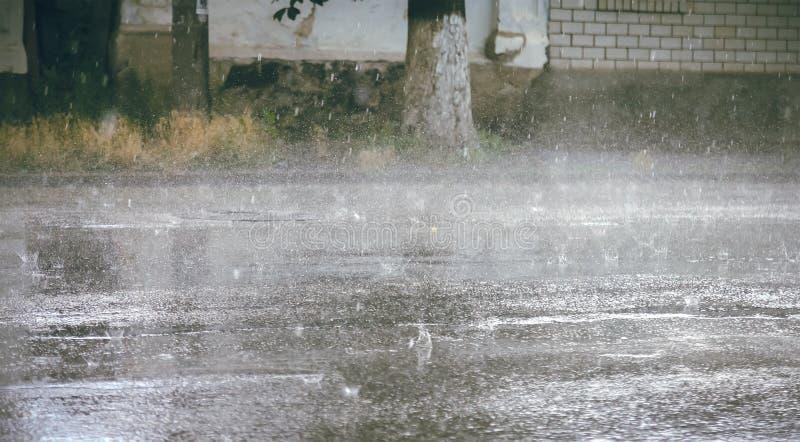 下跌在城市街道上的大雨下落 免版税库存照片