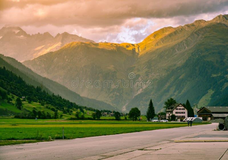 下跌在瑞士村庄的晚上,有阿尔卑斯的倾斜的 图库摄影