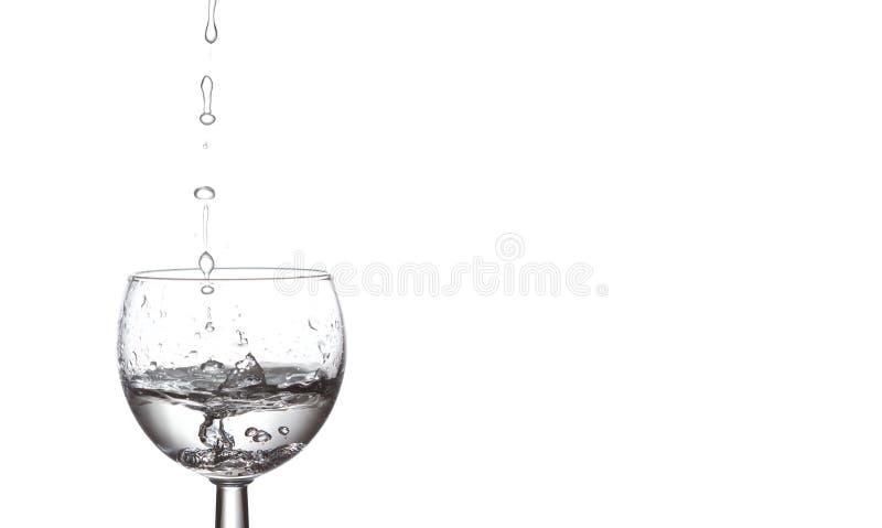 下跌水的滴在玻璃 液体透明的水、飞溅和泡影在白色背景的 复制空间 免版税库存照片