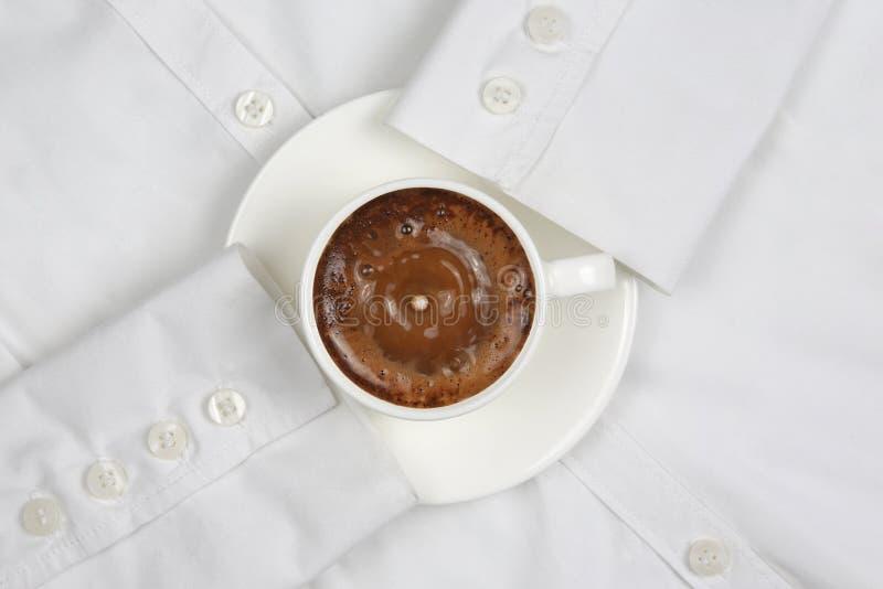 下跌牛奶的下落在一个白色杯子用无奶咖啡 免版税库存图片
