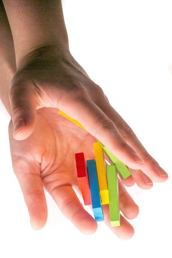 下跌的五颜六色的多米诺在手中 库存照片