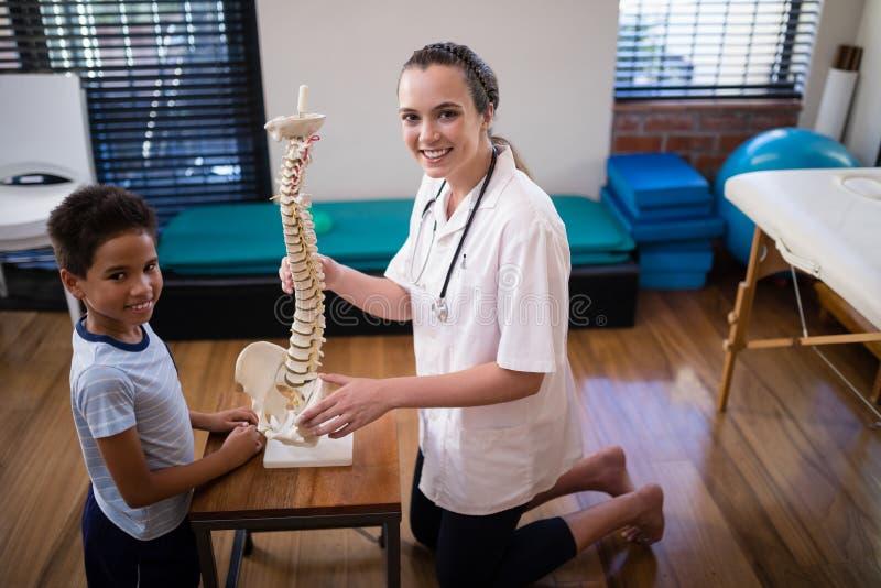 下跪与人为脊椎的微笑的女性治疗师和男孩侧视图画象  免版税库存图片