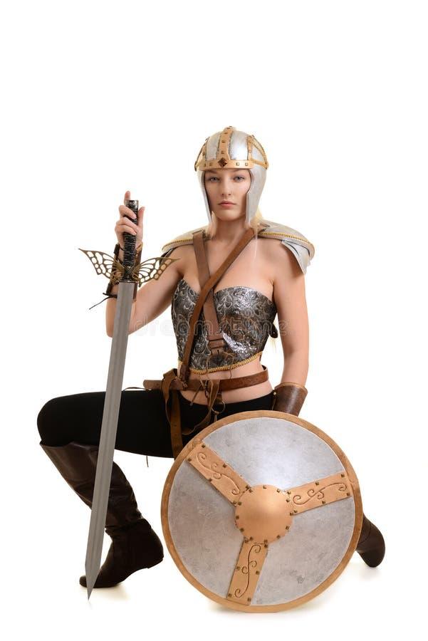 下跪与剑和盾的女性战士 库存图片