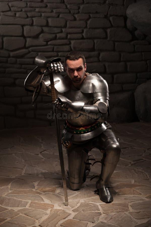 下跪与剑的中世纪骑士 免版税图库摄影