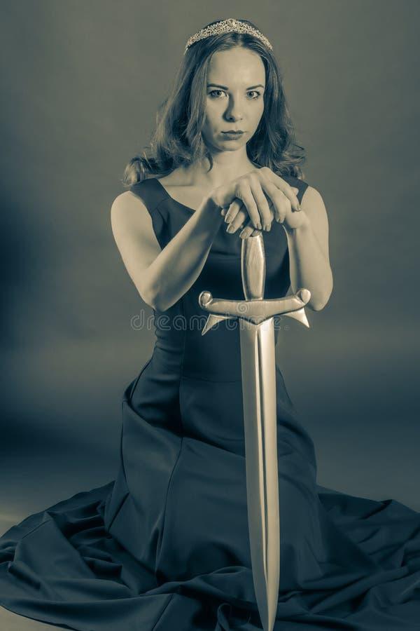 下跪与剑的可爱的公主女孩 免版税库存图片