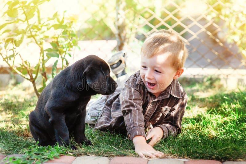 下跪与他的小狗拉布拉多的逗人喜爱的小男孩微笑对照相机 免版税库存图片