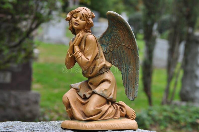 下跪和祈祷在公墓的天使的古铜色雕象 免版税库存照片