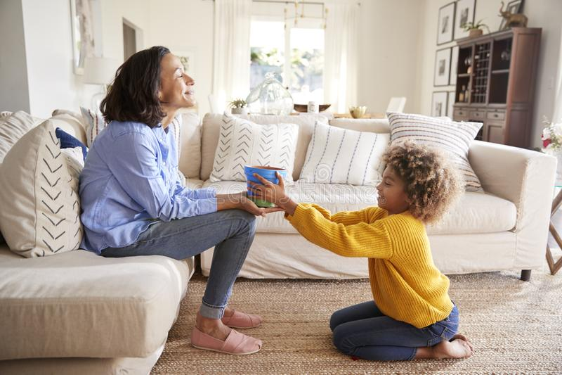 下跪在她的安装的母亲前面的青春期前的女孩给一件手工制造礼物,一个被绘的植物罐,侧视图 免版税库存图片