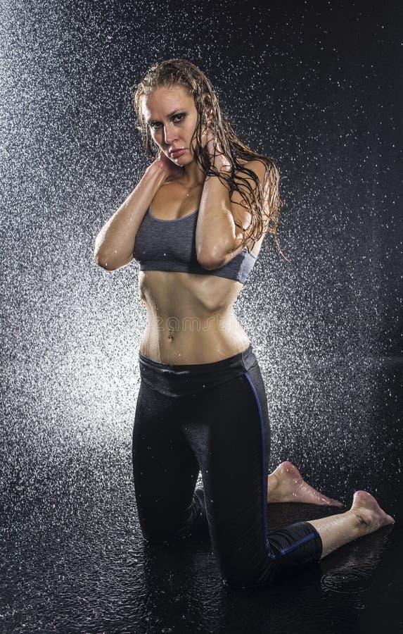 下跪在有喷水的演播室的运动妇女 库存照片