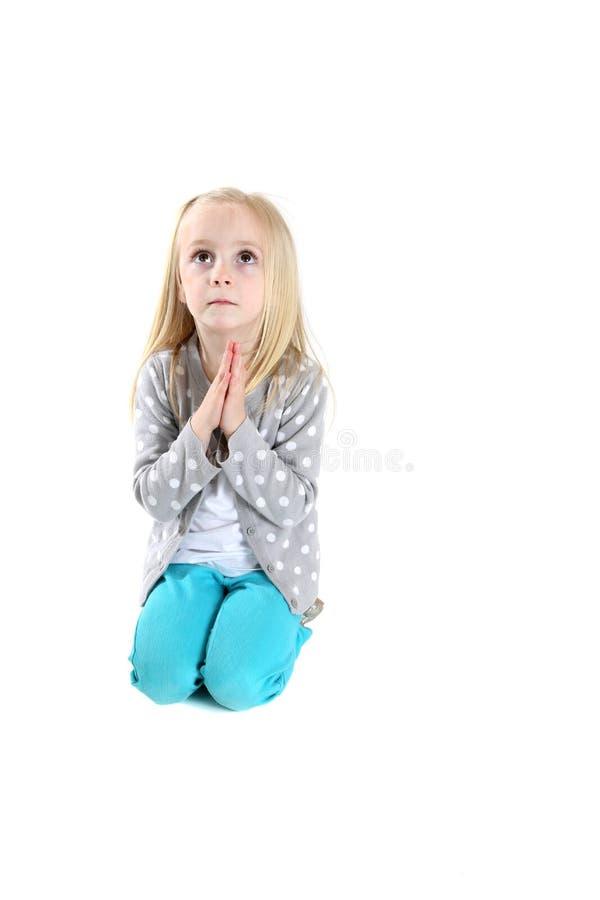 下跪在祷告的可爱的女孩查寻 库存照片
