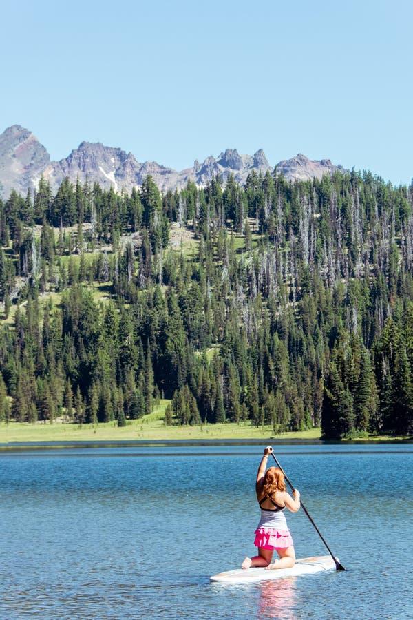 下跪在paddleboard的一个立场的激活适合的红色顶头姜妇女 免版税库存照片