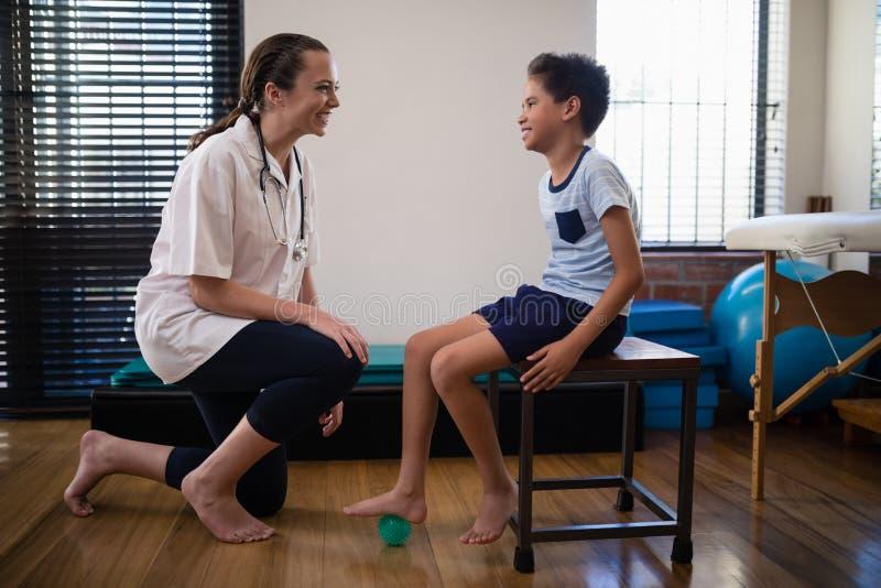 下跪由男孩的微笑的女性治疗师跨步在重音球 免版税库存图片