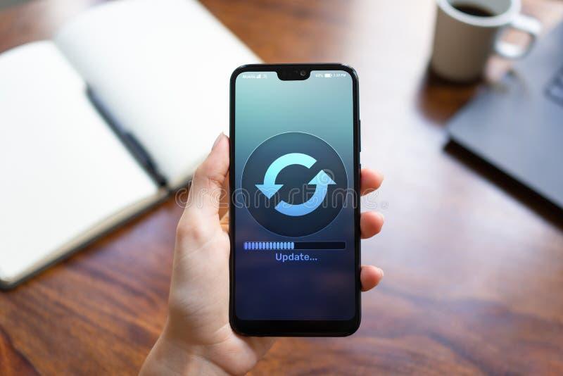下载在智能手机屏幕上的软件更新进展 互联网和技术概念 图库摄影
