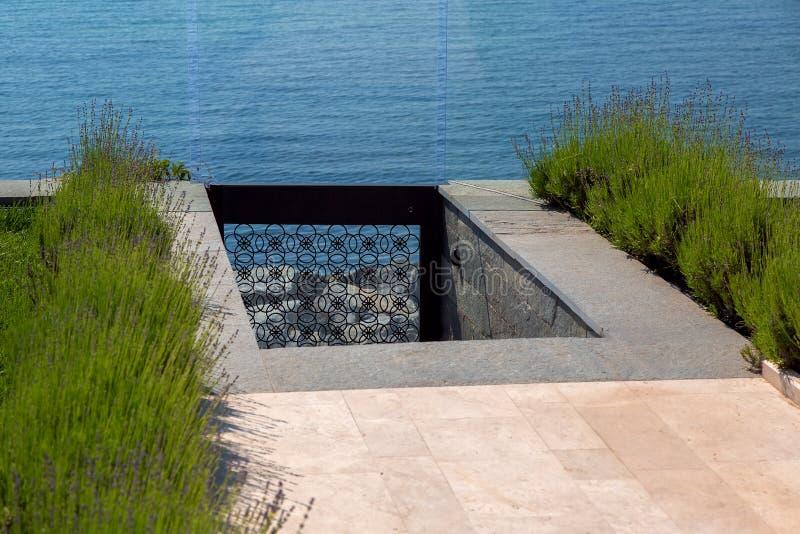 下降向从后院的海有大理石瓦片走道的  免版税库存图片