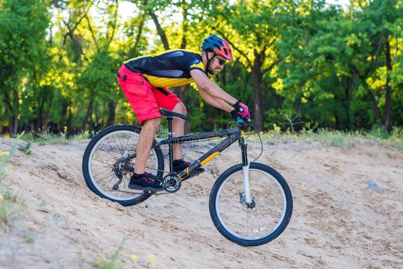下降在登山车的上面,极端体育的专业骑自行车者 免版税库存照片