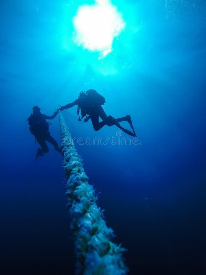 下降的轻潜水员拿着绳索对在红色的一个海难 免版税库存图片