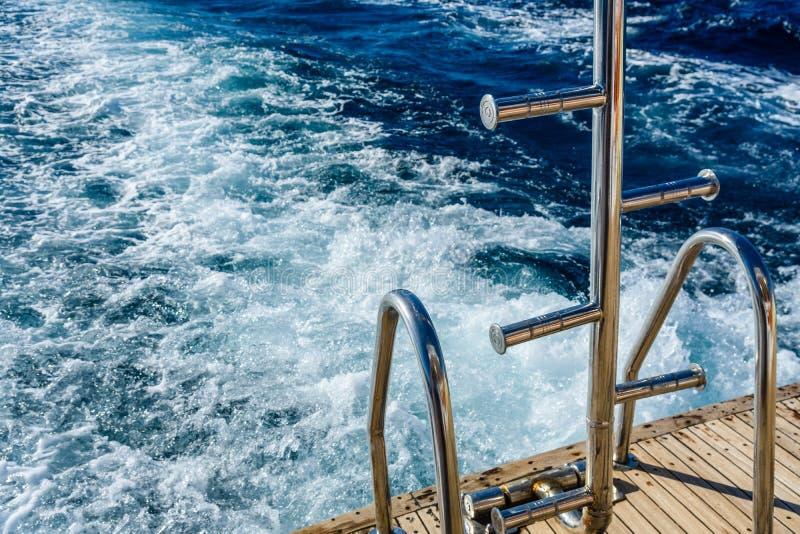 下降的金属楼梯到与白色泡沫的水和波浪踪影里后边水表面上快行游艇 免版税库存照片