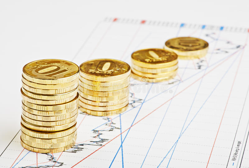 下降趋势在财政图的硬币堆。 库存照片
