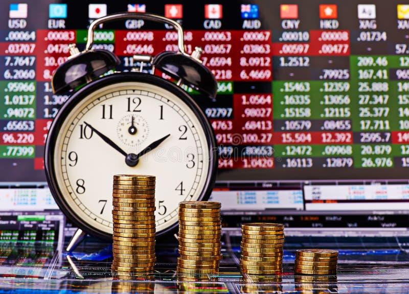 下降趋势堆与闹钟的金黄硬币 免版税库存图片