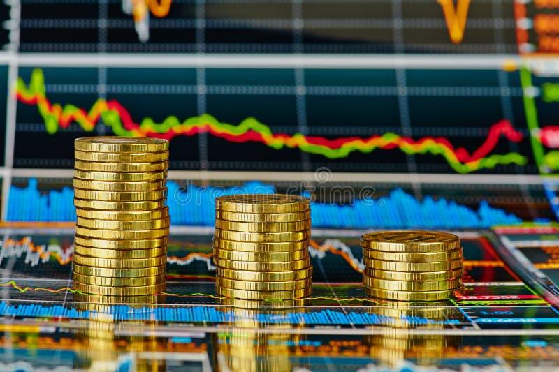 下降趋势财政图和堆金黄硬币 免版税库存图片