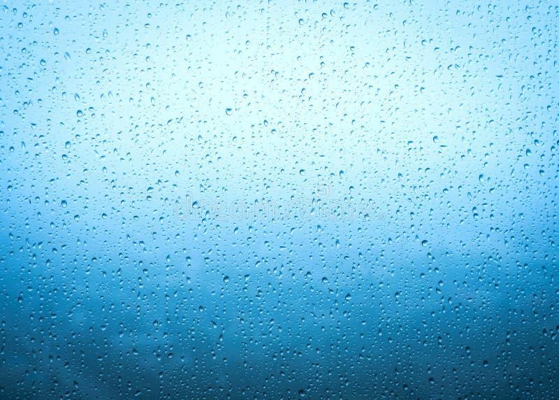 下雨在玻璃窗的下落浮出水面有天空多云背景 免版税图库摄影