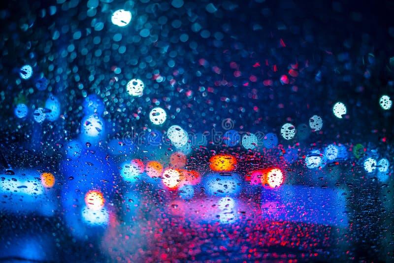 下雨在窗口的下落与路下雨季节的光bokeh 免版税库存图片