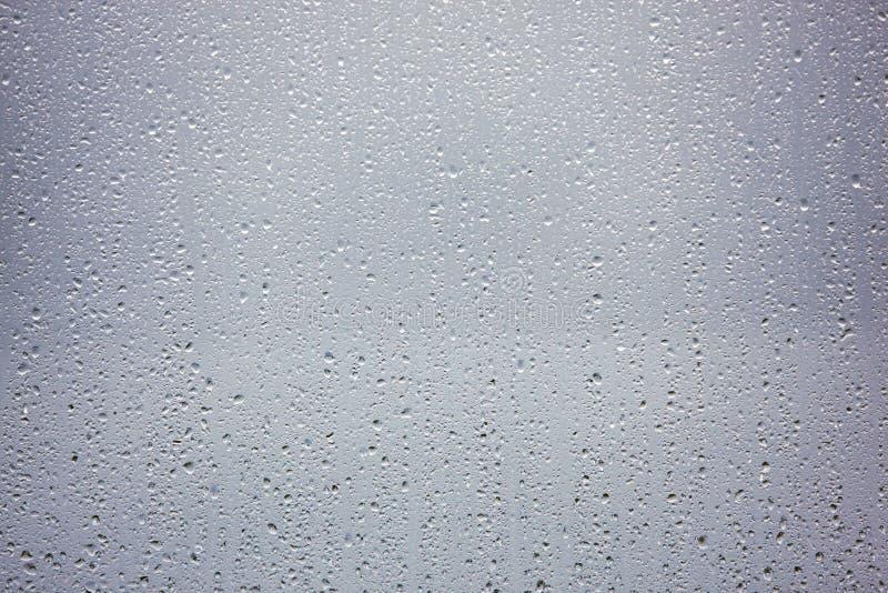 下雨在玻璃窗的下落在一个黑暗的风雨如磐的下午 免版税库存照片
