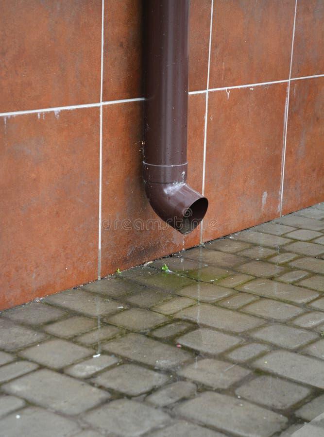 下雨天沟塑料管道,不用排水设备水落管系统,在议院基础附近的路面 免版税库存图片