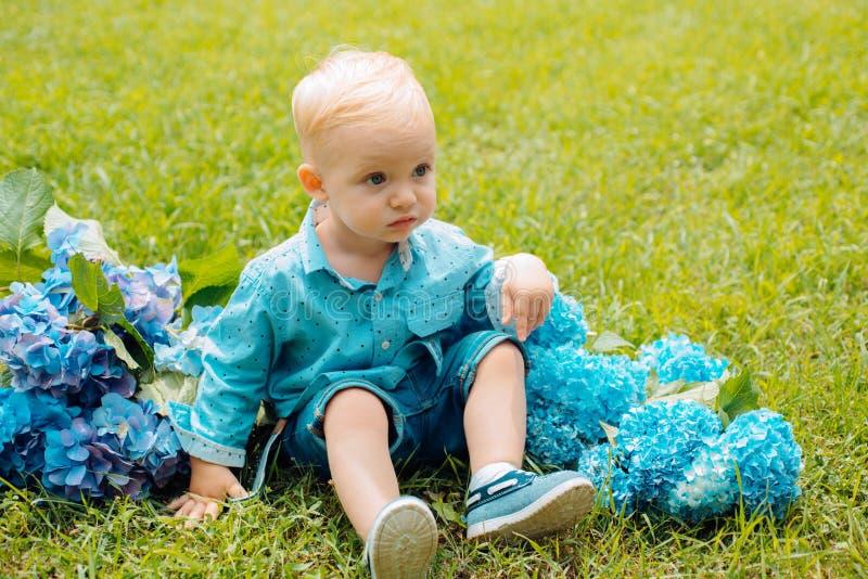 下雨 童年 开花的花的小男孩 夏天 母亲或妇女的天 儿童的日 小的男婴 库存照片