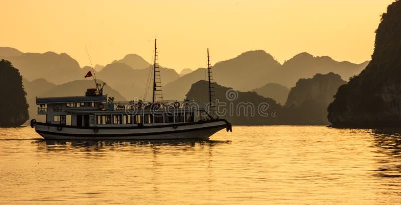 下龙市海湾海岛、游船和海景在晚上与金黄光反射在水,下龙市,越南 免版税库存图片