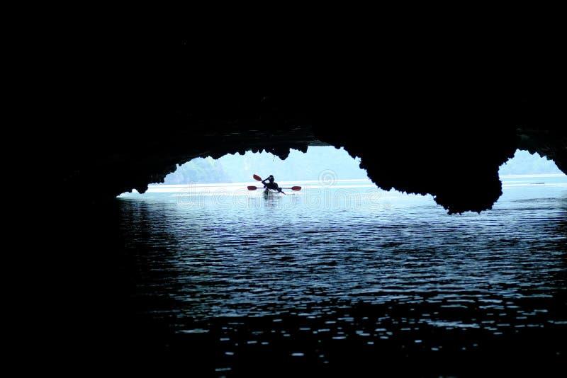 下龙湾/越南,07/11/2017:皮船的两个背包徒步旅行者用浆划通过洞和密集的密林的在下龙湾/猫Ba海岛 免版税库存图片