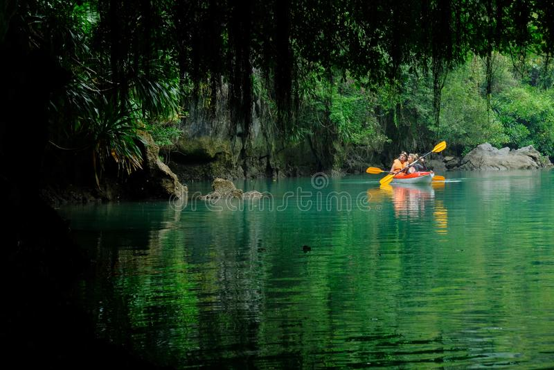 下龙湾/越南,07/11/2017:皮船的两个背包徒步旅行者用浆划通过洞和密集的密林的在下龙湾/猫Ba海岛 免版税库存照片