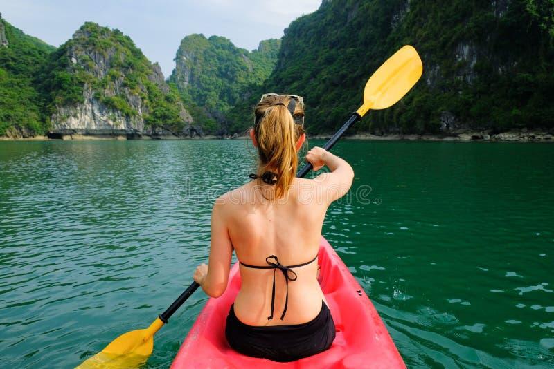 下龙湾/越南,06/11/2017:皮船的妇女用浆划通过石灰岩地区常见的地形海岛和密集的密林的在下龙湾/猫Ba海岛 免版税图库摄影