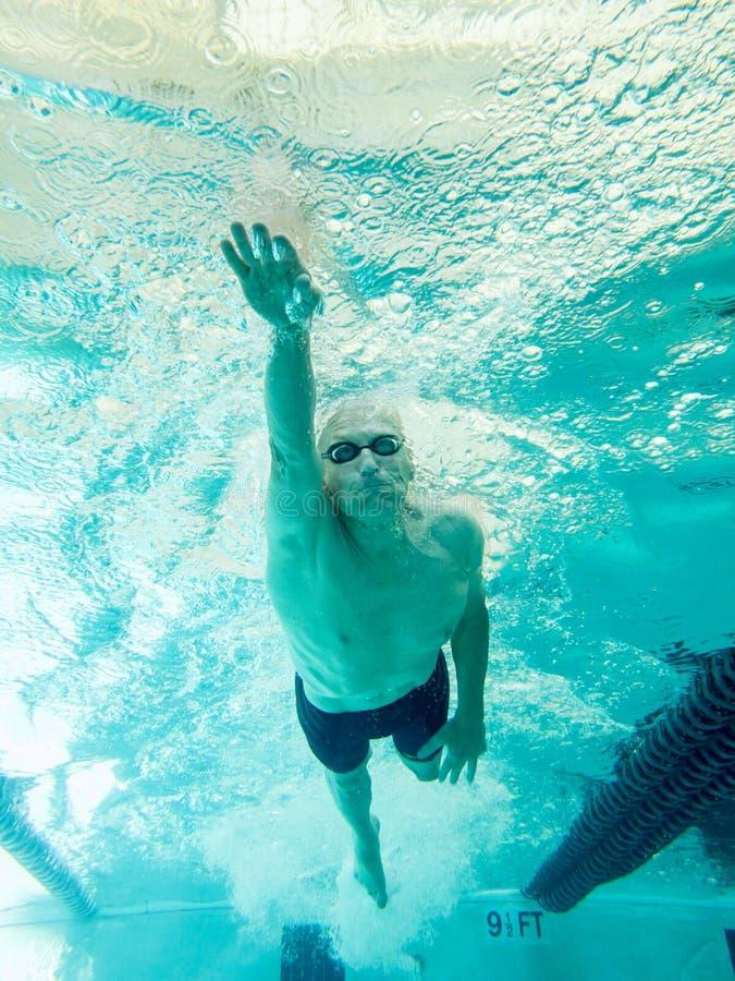 水下更老的资深的游泳者 库存图片
