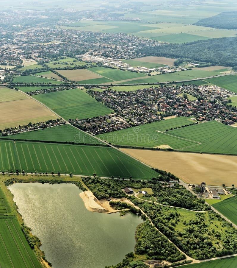 不伦瑞克,有一个充满水的前采石坑在前景,村庄结构与领域和草甸的德国的郊区 库存图片