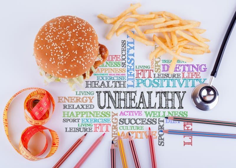 不健康在桌上的题字 健康饮食、生活方式、身体和精神健康概念 免版税库存照片