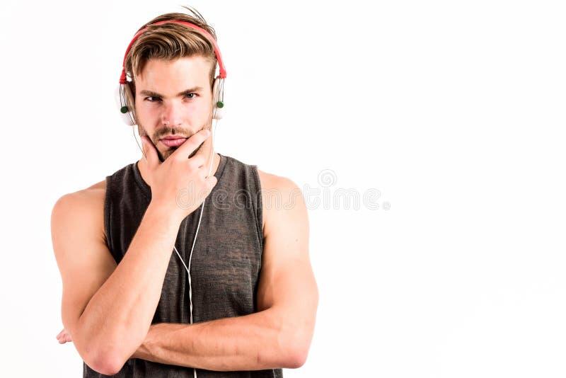 不剃须的在耳机的人听的音乐 性感的肌肉人听体育音乐 在白色隔绝的耳机的人 库存照片