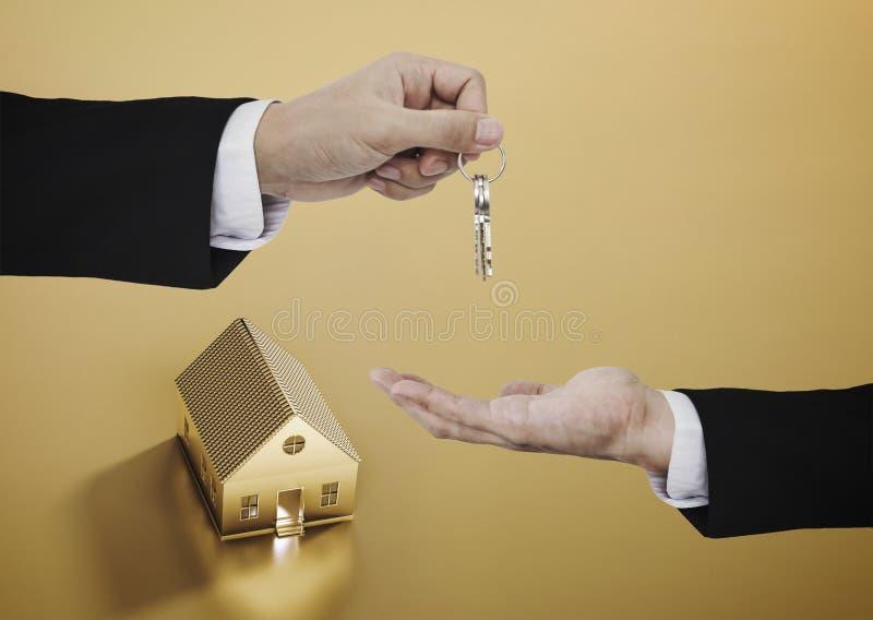 不动产事务、住宅租务和投资 商人移交钥匙有金黄房子背景 免版税库存照片