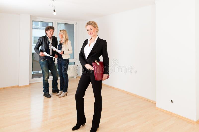 寻找与女性地产商的年轻夫妇房地产 库存图片