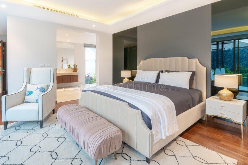 不动产豪华室内设计在水池别墅卧室与舒适国王床的 免版税库存图片